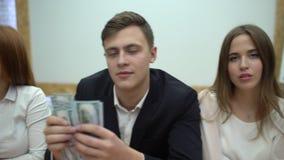 Geschäftsteam Show-Dollar-Geld-Bargeld in der Hand 4 glückliche Manager k, die einen Fan von Dollar wellenartig bewegen Geschäft  stock video footage