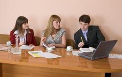 Geschäftsteam sitzt am Tisch Lizenzfreies Stockbild