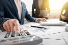 Geschäftsteam unter Verwendung eines Taschenrechners, zum der Zahlen auf seinem zu berechnen Stockfoto