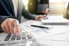 Geschäftsteam unter Verwendung eines Taschenrechners, zum der Zahlen auf seinem zu berechnen Stockfotografie