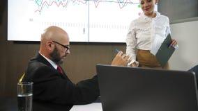 Geschäftsteam, welches die Darstellung eines neuen Finanzprojektes auf einem Arbeitsplatz im Büro in der Zeitlupe bespricht stock video