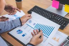 Geschäftsteambesprechung, die mit neuen Startprojekt-, Diskussions- und Analysedaten die Diagramme und die Diagramme, Computer mi lizenzfreies stockfoto