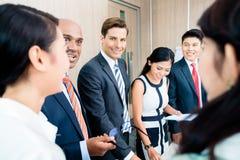 Geschäftsteambesprechung von asiatischen und kaukasischen Führungskräften Lizenzfreie Stockfotos