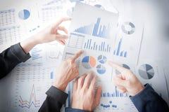 Geschäftsteamhände am Arbeiten mit Unternehmensplan auf Schreibtisch Lizenzfreies Stockbild