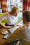 Geschäftstreffen in einem Café Verärgerte Frau betrachtet Mann Ausfall-Konzept stockfoto