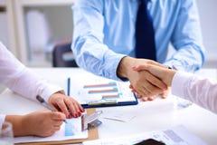 Geschäftstreffen am Tisch, der Hände rüttelt stockfoto