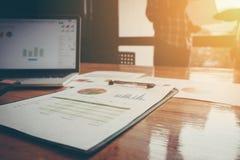 Geschäftsunterlagen auf Bürotisch und Team von Geschäftsleuten O Lizenzfreie Stockbilder