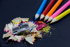 Geschärfte bunte Bleistifte, die von der Ecke, vom metallischen Bleistiftspitzer und von den bunten Bleistift-Schnitzeln auf Schw Stockbilder