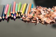 Geschärfte bunte Bleistifte und Schnitzel Stockfotos