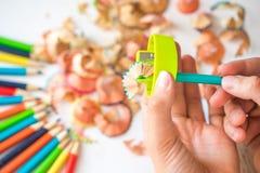 Geschärfter Farbbleistift und Bleistiftschnitzel, Hände eines Kindes auf einem weißen Hintergrund Lizenzfreies Stockfoto