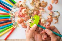 Geschärfter Farbbleistift und Bleistiftschnitzel, Hände eines Kindes auf einem weißen Hintergrund Stockfotos