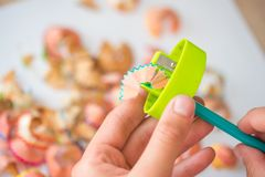 Geschärfter Farbbleistift und Bleistiftschnitzel, Hände eines Kindes auf einem weißen Hintergrund Stockbild