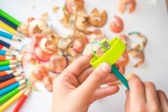 Geschärfter Farbbleistift und Bleistiftschnitzel, Hände eines Kindes auf einem weißen Hintergrund Lizenzfreie Stockfotografie