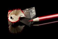 Geschärfter roter Bleistift mit Bleistiftspitzer und Schnitzeln Lizenzfreies Stockbild