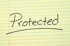 Geschützt auf einem gelben Kanzleibogenblock Lizenzfreies Stockfoto