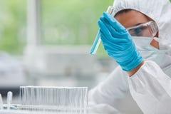Geschützter Wissenschaftskursteilnehmer, der ein Reagenzglas betrachtet Stockfotografie