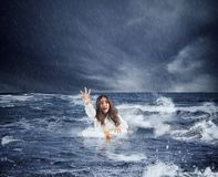 Gesch?ftsfrau im Ozean mit Rettungsg?rtel bittet um Hilfe w?hrend eines Sturms lizenzfreie stockfotografie
