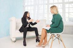 Gesch?ftsfrau mit Nervenzusammenbruch spricht mit dem Psychologen, der Kenntnisse nimmt stockfotos