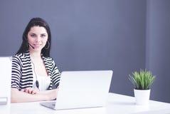 Gesch?ftsfrau Sitting At Desk im B?ro unter Verwendung des Laptop-tragenden Kopfh?rers stockbild
