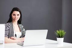 Gesch?ftsfrau Sitting At Desk im B?ro unter Verwendung des Laptop-tragenden Kopfh?rers lizenzfreie stockbilder