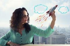 Gesch?ftsfrau startet seine Firma mit einer Rakete Konzept des Starts und der Innovation lizenzfreie stockbilder