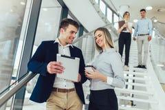 Gesch?ftsfrau und Mann ihre Holding eine Tablette in den H?nden und L?cheln an der Kamera Im Hintergrund sind Gesch?ftsleute stockbilder