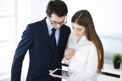 Gesch?ftsm?nner und Frau, die Tablet-Computer im modernen B?ro verwendet Kollegen oder Unternehmensmanager am Arbeitsplatz partne lizenzfreie stockfotografie