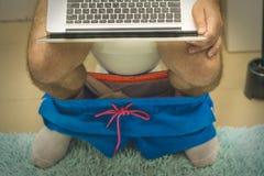 Gesch?ftsmann arbeitet mit Laptop beim Sitzen auf der Toilette stockfotos