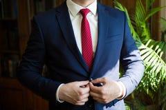 Gesch?ftsmann in der blauen Klage, welche die Krawatte bindet r Br?utigam in einer Jacke Der Morgen des Br?utigams stockbilder