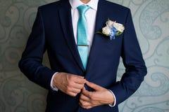 Gesch?ftsmann in der blauen Klage, welche die Krawatte bindet r Mann, der zur Arbeit fertig wird Der Morgen des Br?utigams lizenzfreie stockbilder