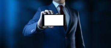 Gesch?ftsmann, der Smartphone h?lt Mann unter Verwendung des Telefons mit lokalisiertem Schirm im Büro lizenzfreie stockbilder
