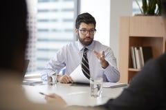 Gesch?ftsmann With Paperwork Sitting bei Tisch, das Kollegen im modernen B?ro trifft stockfoto