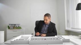Gesch?ftsmann schaut die Architektur, die mit vergr??erter und Mischwirklichkeit projektiert wird stock footage