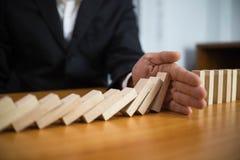 Gesch?ftsmannhand stoppt ununterbrochene umgeworfene Bedeutung des Dominos, die Unternehmenszusammenbruch hinderte Halt ?ber dies lizenzfreie stockfotos