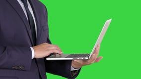 Gesch?ftsmannstellung und mit Laptop auf einem gr?nen Schirm, Farbenreinheits-Schl?ssel stock footage