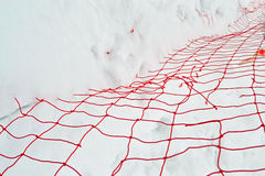 Geschädigtes rotes Garngitter unter weißem Schnee, Winterjahreszeit, Stockfoto
