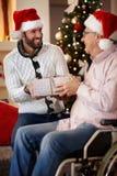 Geschenk auf Weihnachtsdem lächelnden Sohngeben dem Vater vorhanden teilen Lizenzfreie Stockfotos