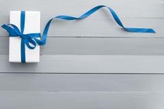Geschenk in der weißen Verpackung und in einem blauen Band Lizenzfreie Stockbilder