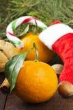 Geschenk in der Weihnachtssocke - Tangerine, Süßigkeit, Nüsse, Zimt Stockfotografie