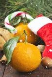 Geschenk in der Weihnachtssocke - Tangerine, Süßigkeit, Nüsse, Zimt auf einem d Lizenzfreies Stockbild