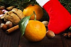 Geschenk in der Weihnachtssocke - Tangerine, Süßigkeit, Nüsse, Zimt auf einem d Stockfotos