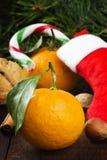 Geschenk in der Weihnachtssocke - Tangerine, Süßigkeit, Nüsse, Zimt auf einem d Lizenzfreies Stockfoto