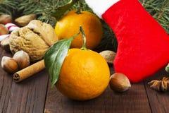Geschenk in der Weihnachtssocke - Tangerine, Süßigkeit, Nüsse, Zimt auf einem d Stockfoto