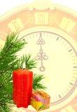 Geschenk, eine Kerze, ein Zweig der Kiefer und eine alte Borduhr Lizenzfreie Stockbilder