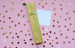 Geschenk in einem goldenen Kasten auf einem rosa Hintergrund mit einer Anmerkung stockfotografie