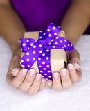 Geschenk in einer Frauenhand Lizenzfreie Stockfotos