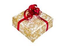 Geschenk eingewickelt im gold-weißen Papier mit einem roten Band Stockfoto