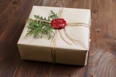 Geschenk eingewickelt im Kraftpapier, gebunden mit Schnur und geklebtem Wachssiegel Lügen auf der Tabelle Stockbild