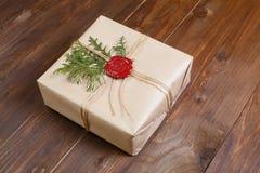 Geschenk eingewickelt im Kraftpapier, gebunden mit Schnur und geklebtem Wachssiegel Lügen auf der Tabelle Stockbilder