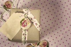Geschenk eingewickelt im recyclebaren Papier, Bänder, verziert mit hölzernem Stockbilder